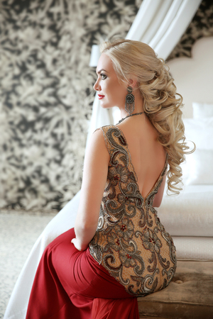 jewlery: Elegant hairstyle. Beautiful blond woman in fashion red dress sitting on modern sofa at luxurious interior apartment with furniture. Stock Photo