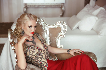 Fashion beauty portrait of beautiful sensual blond woman with makeup Elegant Lady in Prom Evening Party dress sitting in modern armchair with sliver frames. Stockfoto