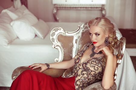 mujeres elegantes: Dama elegante. Moda hermosa mujer rubia sensual con maquillaje en un vestido de fiesta de lujo con bijou, que presenta en la butaca moderna con los marcos de la astilla.