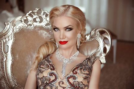 Fashion indoor portrait of beautiful sensual blond woman with makeup in luxurious dress with bijou, posing on modern armchair with sliver frames. Stock Photo
