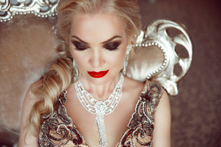 sensual: Fashion indoor portrait of beautiful sensual blond woman with makeup in luxurious dress with bijou, posing on modern armchair with sliver frames. Stock Photo