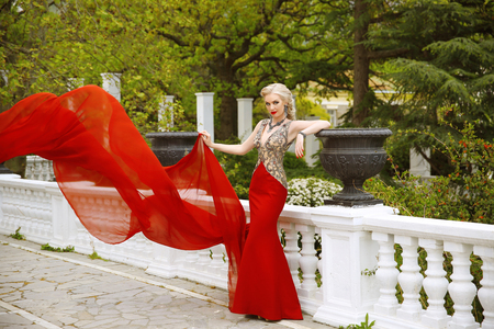 adult mermaid: Fashion outdoor photo of beautiful sexy woman in gorgeous mermaid red dress with waving flying fabric. Elegant model posing on the balcony over green park.