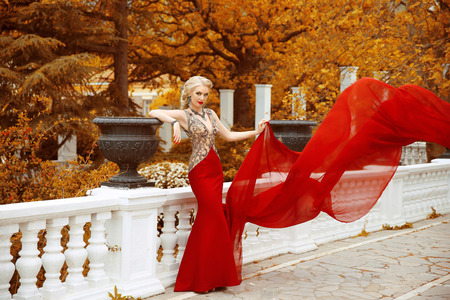 Fashion gorgeous woman in fluttering dress. Beautiful elegant lady wearing in long mermaid red gown in autumn park, Glamorous outdoor full length portrait.