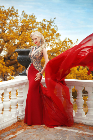 adult mermaid: Sexy young beauty woman in fluttering red dress. Elegant slim lady posing on the balcony with baluster over autumn park view.