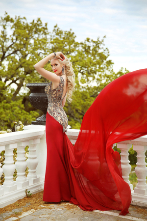 balcony view: Gown. Beautiful sexy young woman model in elegant mermaid blowing red dress posing on the balcony with park view. Stock Photo