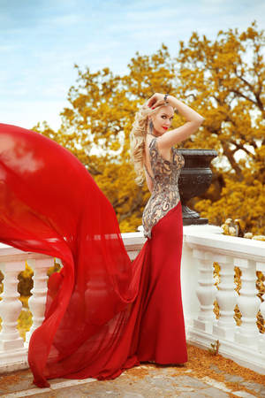 lady in red: Beautiful gorgeous sexy Woman in elegant mermaid red dress with blowing on the balcony over autumn park view. Blond lady with wedding curly hair style  in long gown. Stock Photo