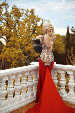 woman dress: Sexy back young beauty woman in mermaid red dress. gorgeous fashion blond girl model with long curly elegant hairstyle. outdoor autumn portrait.