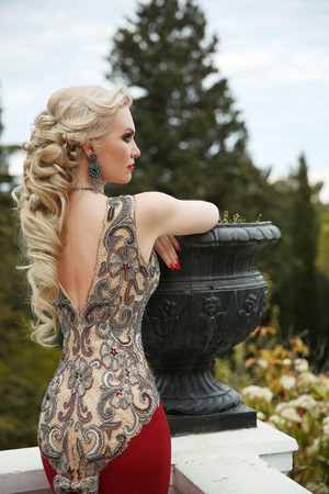 Elegant healthy hairstyle. Sexy lady. beauty gorgeous young woman in fashion luxury dress  leaning on vase. outdoor portrait. Stockfoto