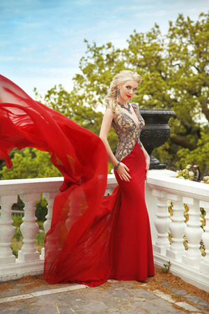 decorative balcony: Fashion beauty outdoor portrait of beautiful woman in red dress posing on the balcony with balustrade and decorative vase in park.
