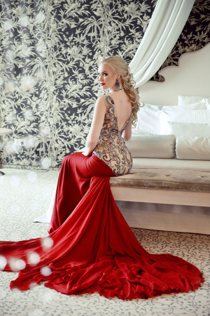 bed skirt: Elegant blond woman model wearing in luxurious red gown with long train of dress sitting at modern interior apartment. Hairstyle.