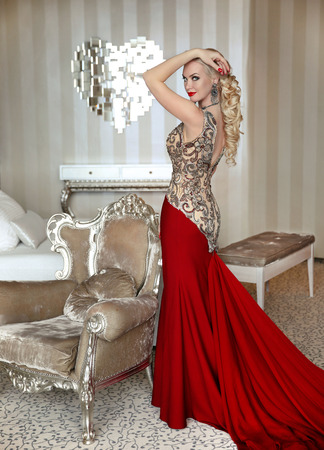 Fashion beautiful blond Girl model with elegant hairstyle in red luxurious gown with long train of dress. Lady by modern armchair at interior apartment