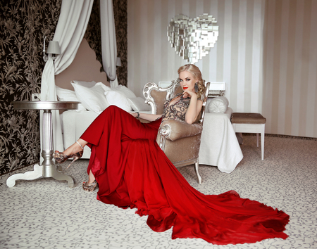 Beautiful adult woman in fashion red dress sitting on modern armchair at luxurious interior apartment with furniture.