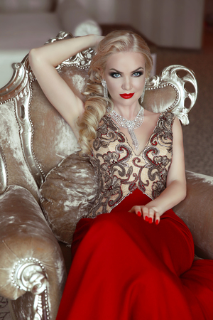 Fashion indoor portrait of beautiful sensual blond woman with makeup in luxurious dress with bijou, posing on modern armchair with sliver frames. Stockfoto