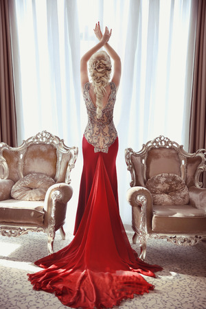 Indoor full length portrait of elegant blond woman in red gown with long train of dress posing between two modern armchairs in front of window at interior.
