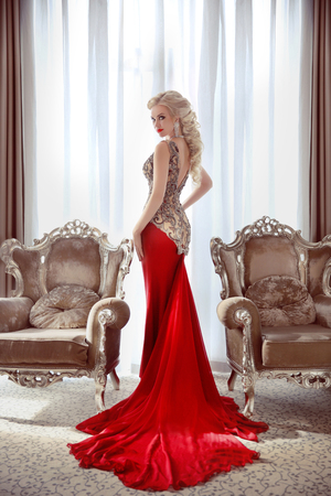 Elegant lady. Beautiful blond woman model in fashion dress with long red train posing between two modern armchairs in front of window at interior. Фото со стока