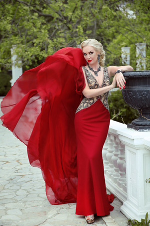 Fashion elegant blond woman model in red gown with blowing fabric. Outdoor full length portrait photo. Stockfoto