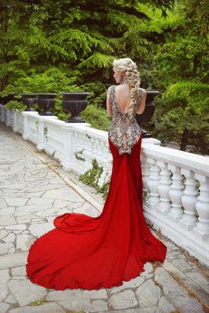 ドレスの長い列車と赤いドレスでエレガントなブロンド女性ファッションモデル屋外のフルの長さの肖像画の写真。