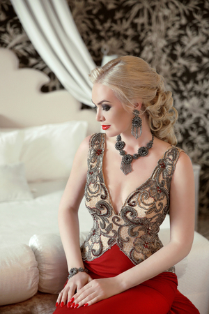 Indoor beauty portrait of blond woman in fashion jewelry and luxurious dress posing on bed at interior.