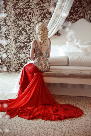 Elegant  blond woman model wearing in luxurious red gown with long train of dress sitting at modern interior apartment. Hairstyle.