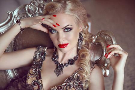 Mode indoor portret van mooie sensuele blonde vrouw met make-up in een luxe jurk met bijou, die zich voordeed op moderne fauteuil met zilver frames.