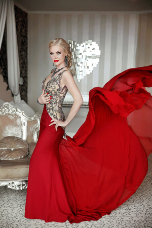 Attractive blond woman model wearing in elegant dress with blowing red skirt at modern interior with luxurious furniture. Stockfoto