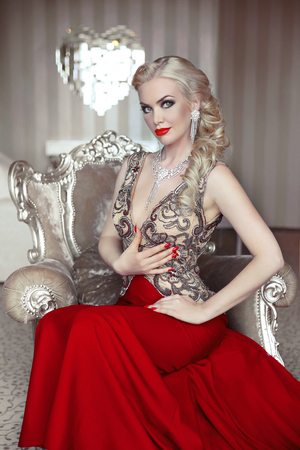 Fashion model portrait of beautiful sensual blond woman with makeup in luxurious dress with bijou, posing on modern armchair with sliver frames. Indoor photo