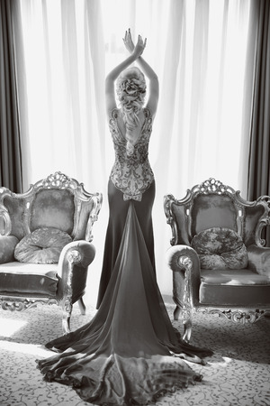 sensual woman: Fashion beautiful sensual woman in luxurious dress with long train, posing between two modern armchairs in front of window at interior. indoor full length portrait