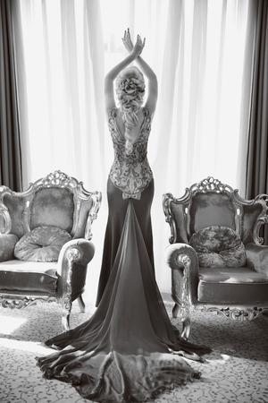 mooie vrouwen: Mode mooie sensuele vrouw in een luxe jurk met lange trein, die zich voordeed tussen twee moderne leunstoelen voor venster in het interieur. indoor volledige lengte portret