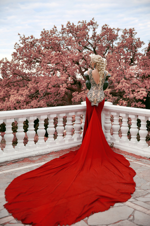 red dress: Fashion elegant blond woman model in red gown with long train of dress. Outdoor full length portrait photo.