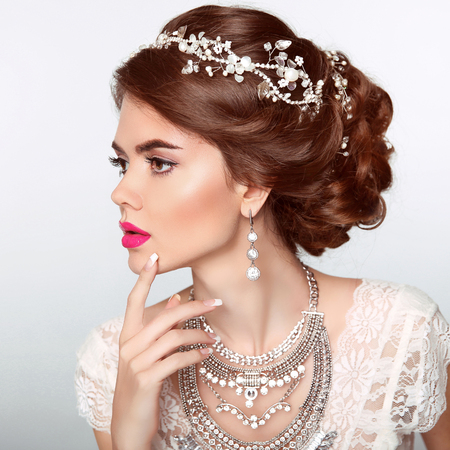Wedding Hairstyle. Beautiful fashion bride girl model portrait. Luxury jewelry. Attractive young woman with red hair. Foto de archivo
