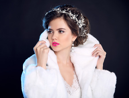 winter fashion: Fashion girl model in white fur coat, luxury jewelry, elegant hairstyle, makeup. Trendy brunette woman posing isolated on dark background. Winter portrait.