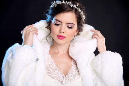 Beauty Fashion Model Girl in Mink Fur Coat and white furry hood. Makeup. Beautiful Luxury Winter Woman isolated on black background. Stock Photo