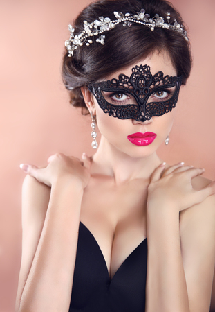Elegant hairstyle. Beautiful Girl in black veil mask. Masquerade. Makeup. Hairstyle. Jewelry.