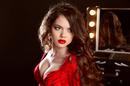 sexy dress: Beautiful woman with sexy lips in red dress posing in dressing room. Beauty fashion portrait. Attractive Lady against of mirror with bulbs for makeup.