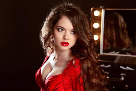 labios sexy: Hermosa mujer con los labios sexy en vestido rojo posando en el vestidor. Retrato de la moda belleza. Señora atractiva en contra de espejo con bombillas para el maquillaje.