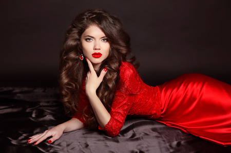 Beauty Fashion Portrait. Beautiful Woman with Curly Hair wearing in fashion red dress. elegant girl lying on the black satin floor. manicured nails Stock Photo