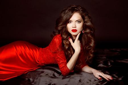 belle brune: Beau modèle élégante femme brune vêtue à la mode robe rouge avec le maquillage, la coiffure ondulée sain et ongles manucurés, fille couchée sur le plancher de satin noir. Banque d'images