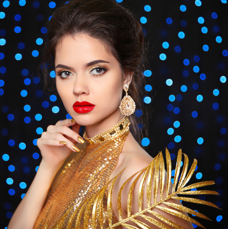 women face stare: Beauty Portrait of a beautiful fashion girl model with red lips makeup, luxury jewelry, manicured nails. Elegant young woman posing in golden dress over blue holiday lights background.