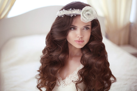 coloring lips: Healthy hair. Beautiful bride girl fashion portrait. Wedding Hairstyle. Beauty Makeup. Elegant young woman with rose flower in wavy hair. Stock Photo