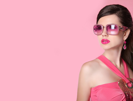 Beauty fashion model girl in sunglasses with bright makeup, long hair, luxury earrings jewelry. Glamour woman isolated on pink studio background. Stock Photo