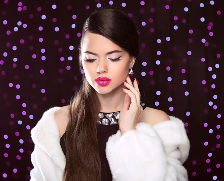 glamour hair: fashion portrait of gorgeous woman with makeup in luxurious fur coat over party holiday lights background.