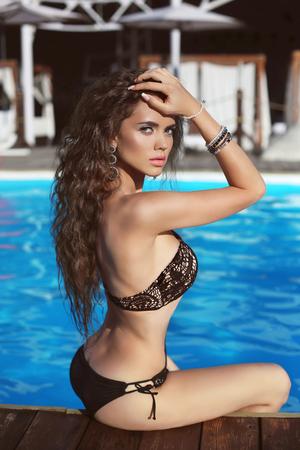 modelos posando: Modelo de Bikini. Bella modelo sexy chica morena con el pelo largo y ondulado, quemaduras de sol por el azul piscina de agua en la playa. Vacaciones. Mujer bronceada.