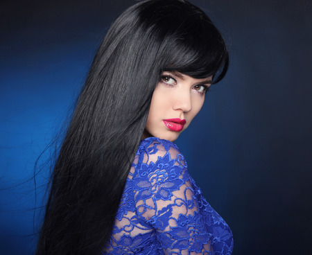 Long Black Hair. Beautiful model girl with healthy straight shiny hair and sensual lips isolated on blue dark background. Beauty Brunette Woman. Stock Photo
