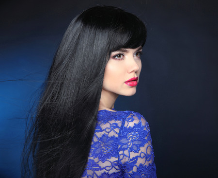 glamour woman: Long Black Hair. Beautiful model girl with healthy straight shiny hair and sensual lips isolated on blue dark background. Beauty Brunette Woman. Stock Photo
