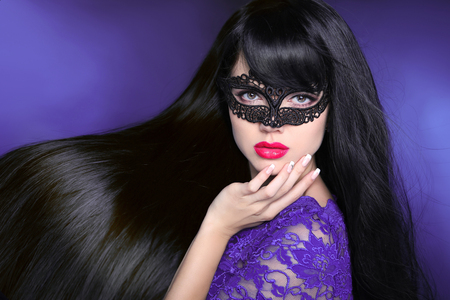 Hair. Beautiful Brunette Girl. Healthy Long glossy Hairstyle. Red lips. Beauty make-up. Mask. Manicured nail. Fashion art photo of young woman isolated on purple dark background. Stock Photo
