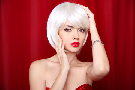 Blond bob hairstyle. Make-up. Beautiful sexy Girl Face Close-up. Red lips. White Short Hair.  Fringe. Vogue Style Woman isolated on curtain or drapes red background. Stock Photo