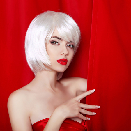 Blond bob hairstyle. Make-up. Beautiful sexy Girl Face Close-up. White Short Hair.  Fringe. Vogue Style Woman isolated on curtain or drapes red background.