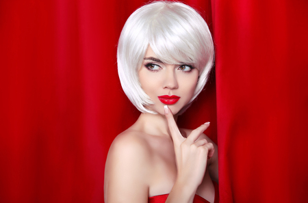 Fashion Beauty Blond Portrait with White Short Hair. Make-up. Beautiful Girl Face Close-up. Hairstyle. Fringe. Vogue Style Woman isolated on curtain or drapes red background. Stock Photo