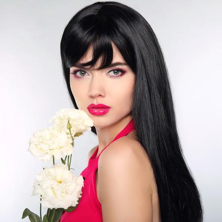 persone nere: Capelli lunghi. Beautiful Fashion Makeup lusso, le ciglia lunghe, pelle perfetta viso make-up. Brunette di bellezza modello della donna con i fiori. Acconciatura sano. Archivio Fotografico