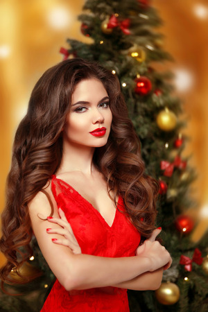 Beautiful smiling girl model. Makeup. Healthy long hair style. Elegant lady in red dress over christmas tree lights background. Party. holidays and people concept
